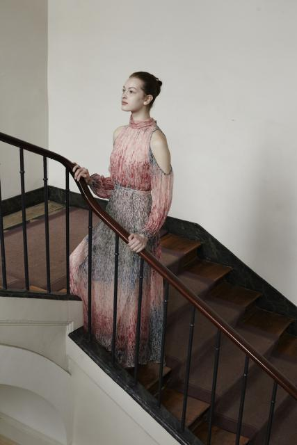 A model poses on the stairs in a dress.